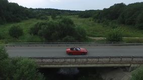 Aerial survey of the car rides on the serpentine. Flying over red cabriolet drive the street.Aerial view of red car. Which goes over the bridge. Traffic on the stock footage