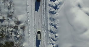 An aerial survey of the car that travels along the snow-covered road. Video shot by drone in 4K stock footage