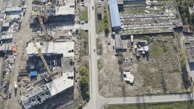 Aerial survey of a construction site with hoisting mechanisms and building materials