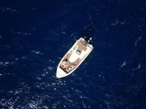 Aerial survey of a couple on a boat sunbathe together on a warm Royalty Free Stock Image