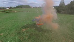 Aerial survey of couple walk on the field with colored smoke in hands. Flying over man and woman run through the field stock video footage