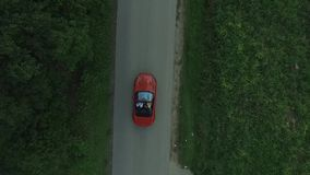 Aerial survey of red cabrioled goes on the road and couple using colored smoke.Flying over classic red convertible car stock footage