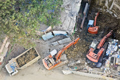 Aerial of three diggers moving earth. Any orientation of construction site in Mumbai India where 3 diggers are moving earth onto a tipper Royalty Free Stock Images