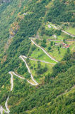Aerial tight view of a zig-zag winding road going up a steep slope near Geiranger, Norway with some traffics Royalty Free Stock Photography
