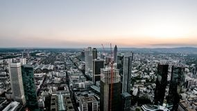 Aerial time lapse of the Frankfurt / Main skyline and site of a skyscraper during sunset on a hot summer day - Germany. Aerial time lapse of the Frankfurt , Main stock footage