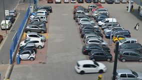 Aerial Time lapse of a people and cars at a busy parking lot during the day. Aerial Time lapse of a people and cars at a busy parking lot during the day stock video