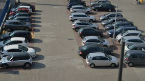 Aerial Time lapse of a people and cars at a busy parking lot during the day. Aerial Time lapse of a people and cars at a busy parking lot during the day stock footage