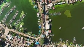 Aerial top down of fisherman huts and docks at river polluted with green algae. Aerial top down of fisherman village with huts and boat docks at river polluted stock video footage