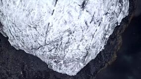 Aerial top down footage of ice glacier next to the lake with snow in the air.