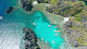 Aerial top down photo of entrance into the Small lagoon in El-Nido, tour A, Palawan. Philippines. Banka boats and kayaks
