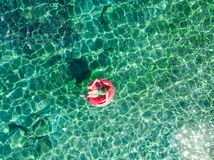 Aerial top down view of cute young girl floating on toy ring at Emplisi Beach, picturesque stony beach in a secluded bay, with stock photography