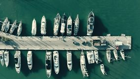 Aerial top down view of docked sailing yachts at marina pier, Greece. Aerial top down view of docked sailing yachts at marina pier stock footage