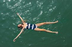 Aerial top down view of a girl in the sea. Aerial top down view of a girl in a white and blue swimsuit in the sea royalty free stock image