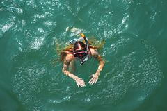 Aerial top down view of a girl wearing swimming mask in the sea. Aerial top down view of a girl in a white and blue swimsuit wearing swimming mask in the sea stock images