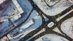 Aerial top down view of intersection in winter, circle crossroad with traffic and snow