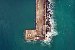 Aerial top down view of old concrete pier or breakwater with lighthouse and emerald sea water with waves. Drone shot stock photography