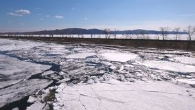 Volga river is partially frozen, big blocks of ice create blue-and-white patchwork. Aerial top down view over icy river surface pattern. Winter season on Volga stock footage