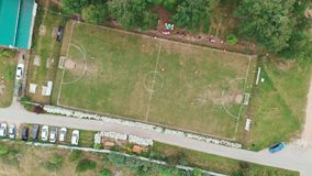 Aerial top down view of soccer field. Non-professional amateur football match. Drone. Aerial top down view of soccer field and two amateur teams playing. Kick stock video footage