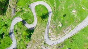Aerial: top down view tailspin over winding mountain road on the Italian Alps, crossing green meadow and pasture in alpine valley,. Adventure road trip in stock image