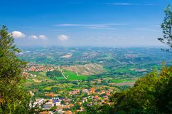Aerial top panoramic view of landscape with valley, green hills, fields and villages of Republic San Marino stock photography