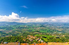 Aerial top panoramic view of landscape with valley, green hills, fields and villages of Republic San Marino suburban district royalty free stock image