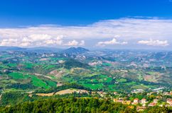 Aerial top panoramic view of landscape with valley, green hills, fields and villages of Republic San Marino stock photos