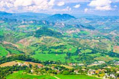 Aerial top panoramic view of landscape with valley, green hills, fields and villages of Republic San Marino stock photo