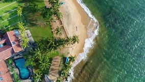 Aerial top shot in motion houses with swing pool near the sandy beach in Sri Lanka. Beautiful houses with swimming pools are located at the very shore washed by stock video footage