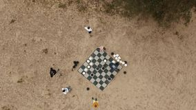 Aerial top shot people set giant chess figures on board at sand beach near tree stock footage