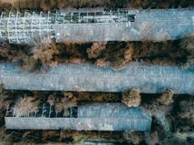Aerial top view of abandoned industrial agricultural buildings among spring forest trees royalty free stock photo