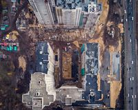 Aerial or top view from above, construction of modern houses or buildings with cranes and other industrial vehicles royalty free stock images