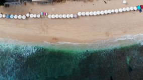 Aerial top view beach with sun parasol and turquoise sea with waves in Bali stock footage