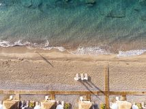 Aerial top view on the beach. Summer time morning. Aerial top view on the beach. Sunbeds, umbrellas, sand and sea waves royalty free stock photos