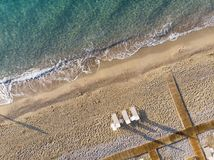 Aerial top view on the beach. Summer time morning. Aerial top view on the beach. Sunbeds, umbrellas, sand and sea waves royalty free stock image