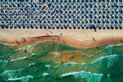 Aerial top view on the beach. Umbrellas, sand and sea waves. Aerial top view on the beach. Umbrellas, sand, happy people and sea waves royalty free stock photography
