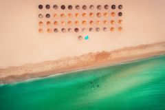 Aerial top view on the beach. Umbrellas, sand and sea waves. Summer stock photos