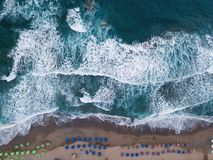 Aerial top view on the beach. Umbrellas, sand and sea waves. Summer vacation stock photos