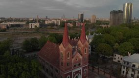 Aerial top view of beautiful church in Riga, European capital during Golden Hour sunset - Martin`s Ev. Lutheran. Spring 2019 stock footage