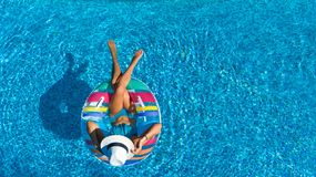 Aerial top view of beautiful girl in swimming pool from above, relax swim on inflatable ring donut and has fun in water Stock Images