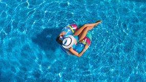 Aerial top view of beautiful girl in swimming pool from above, relax swim on inflatable ring donut in water on family Royalty Free Stock Photography