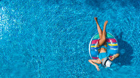 Aerial top view of beautiful girl in swimming pool from above, relax swim on inflatable ring donut in water on family. Aerial top view of beautiful girl in royalty free stock photo