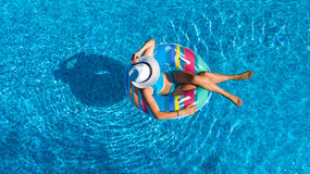 Aerial top view of beautiful girl in swimming pool from above, relax swim on inflatable ring donut in water on family Stock Photos