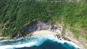 Aerial Top View On Big Ocean Waves And Hidden Paradise Beach Under Big Cliff. Aerial footage of beautiful and wild empty beach with clean yellow sand, turquoise stock video