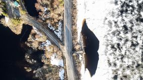 Aerial top view of a branch road, white snowy land and road, trees stock photography