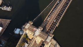 Aerial top view of Brooklyn bridge, with American flag on it. Scenic view of East river in New York, America. Drone flying over the famous sight in USA stock video footage