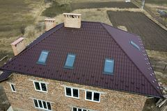 Aerial top view of building steep brown shingle roof, brick chimneys and small attic windows on house top with metal tile roof. Roofing, repair and renovation royalty free stock photography