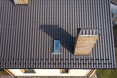 Aerial top view of building steep shingle roof, brick chimneys and small attic window on house top with metal tile roof. Roofing,. Repair and renovation work stock images