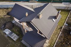 Aerial top view of building steep shingle roof, brick chimneys and small attic window on house top with metal tile roof. Roofing,. Repair and renovation work royalty free stock photography