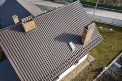 Aerial top view of building steep shingle roof, brick chimneys and small attic window on house top with metal tile roof. Roofing,. Repair and renovation work royalty free stock images