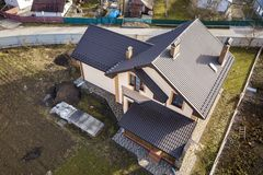 Aerial top view of building steep shingle roof, brick chimneys and small attic window on house top with metal tile roof. Roofing,. Repair and renovation work royalty free stock photo